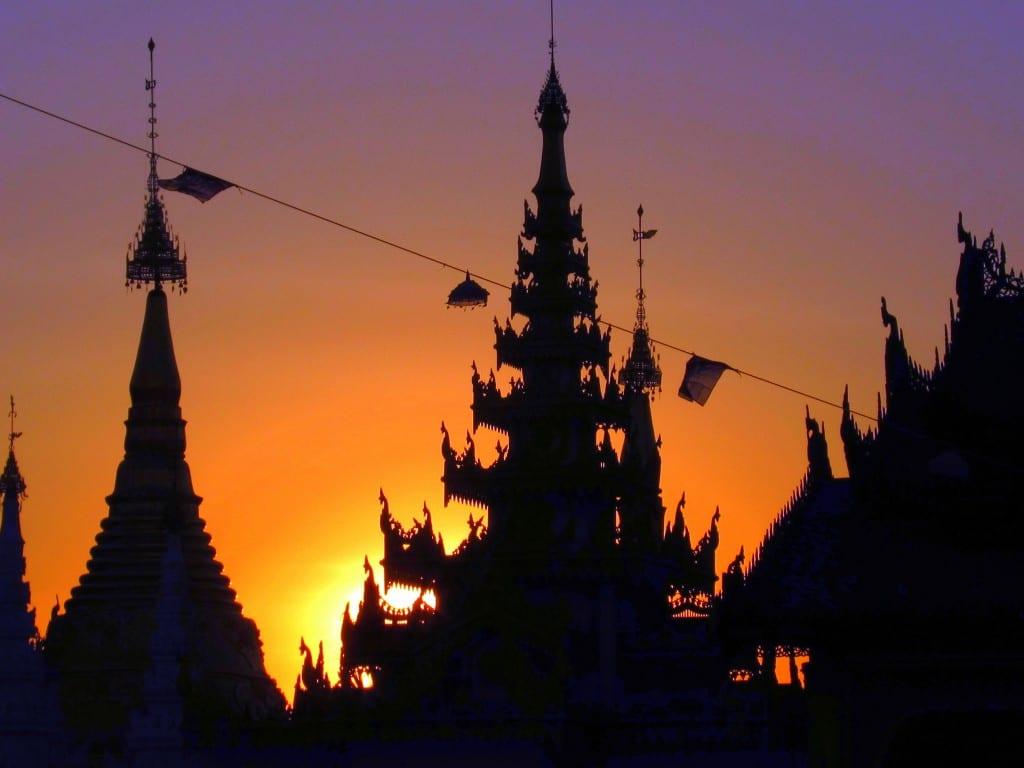 Sun setting behind a zedi at Shwedagon Pagoda