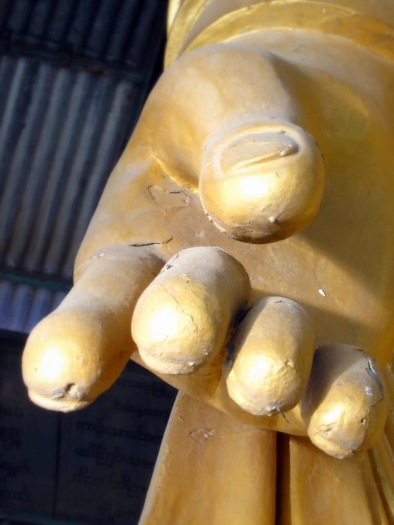 Hand of the standing Buddha, pointing toward the city below