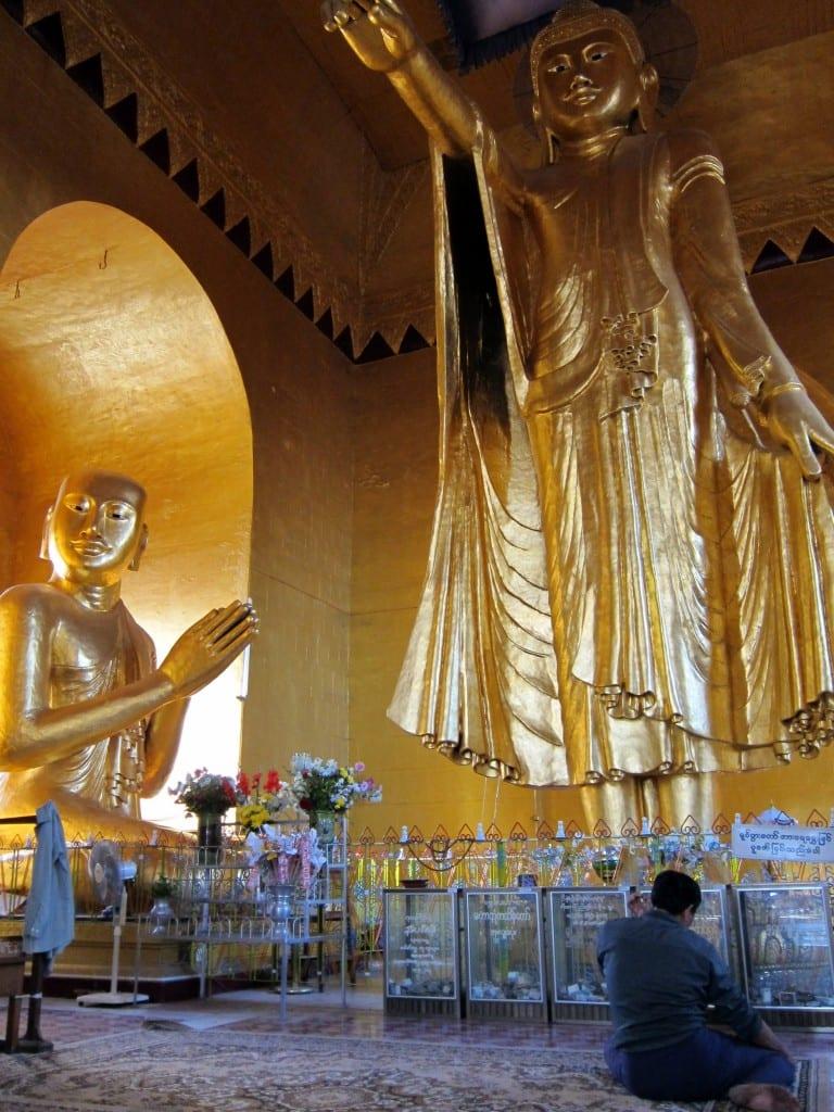 A Burmese man praying at the standing Buddha on Mandalay Hill