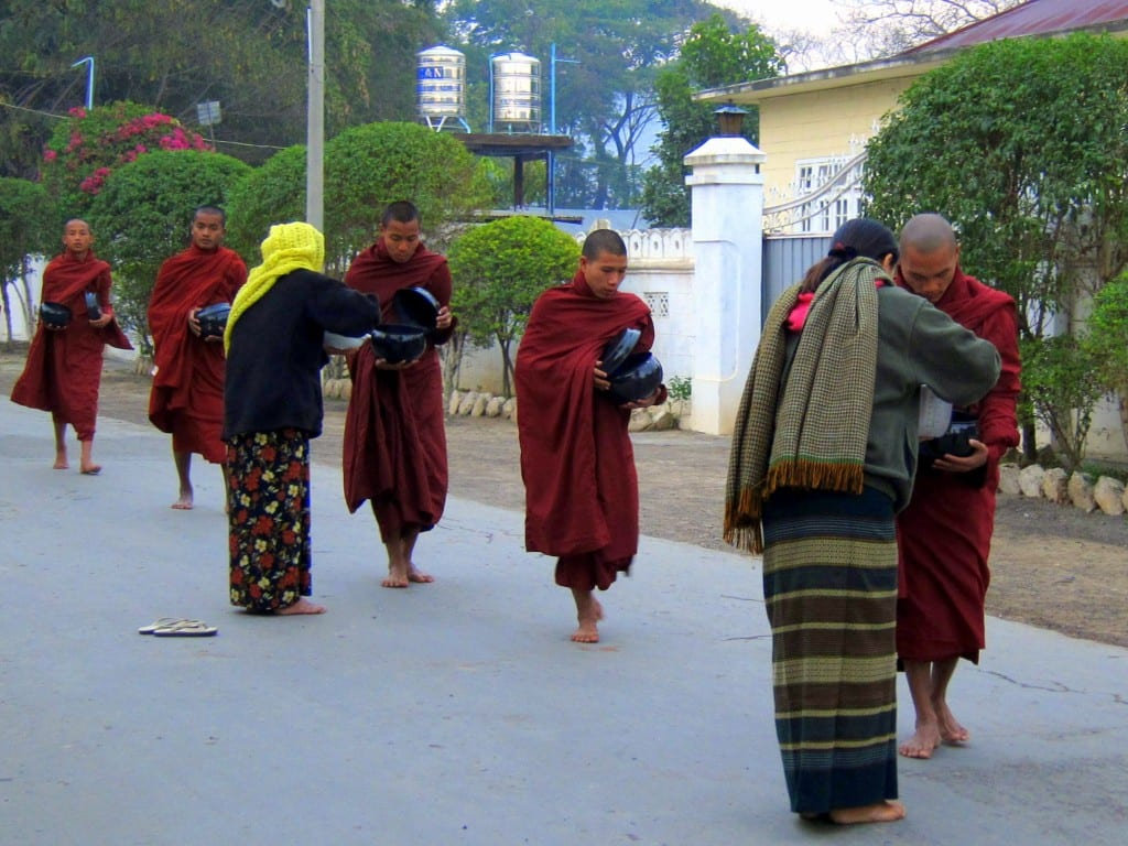Offering alms to the monks in a longyi at dawn on Inle Lake