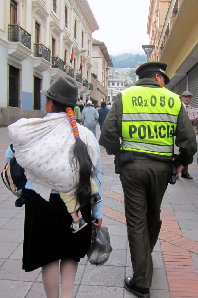 Indigenous woman in her traditional dress walking next to a policeman in the old city in Quito