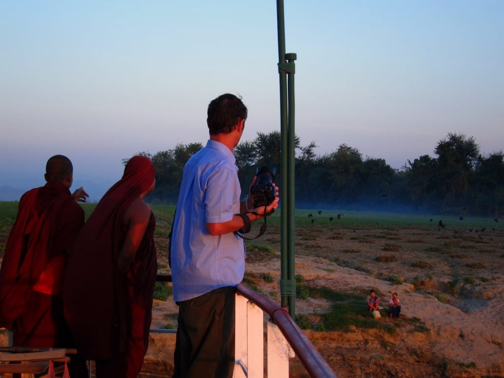 Monks watching dusk fall over the Ayeyarwaddy in Burma