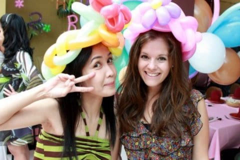 Me and Prae wearing balloon hats at a birthday party